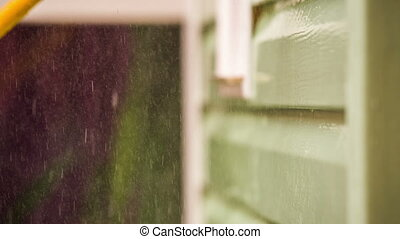 Person Washing House Wall With Jet Of Water And Brush -...