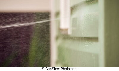 Water Jet Washing House Wall - CLOSE UP: Side view of a...