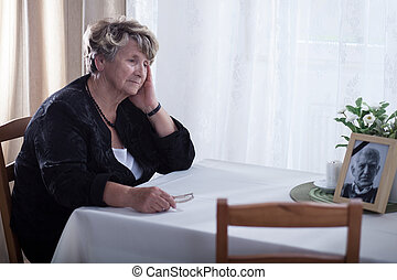 Looking at dead husband's picture - Senior woman looking at...