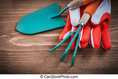 Protective gloves trowel and rake on wooden board