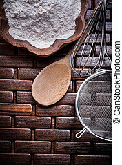 Close up view of wooden spoon bowl flower sieve egg-whisk