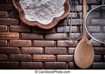 Composition of wooden spoon bowl flower sieve and egg-whisk