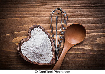 Composition of wooden spoon heartshaped bowl flower...