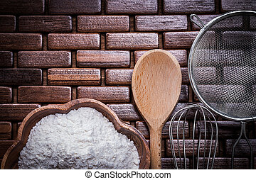 Wood spoon bowl flower sieve and egg-whisk on wooden matting...