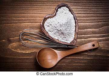 Wooden spoon heartshaped bowl flower egg-whisk on wood board...