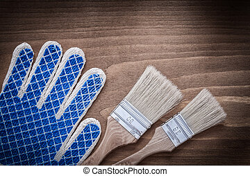 Paintbrushes and protective glove on wooden surface close up...