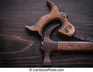 Grunge longstanding handsaw and claw hammer on vintage...