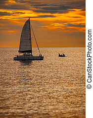 Catamaran Sailboat on a Tropical Sea at Sunset - Sky blazing...