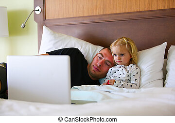 Little girl is watching cartoon with dad while sick - Little...