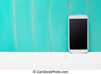 Smart phone on teal wooden background - White smart phone on...