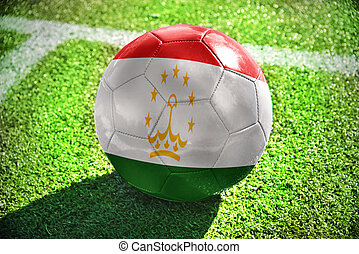 football ball with the national flag of tajikistan lies on...