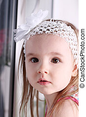 face of cute little blond girl with white headband