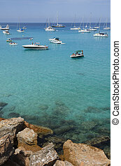 Many boats moored on the blue and green sea near the rocks -...
