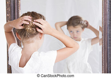 Child fixing her hair while looking in the mirror - Child or...