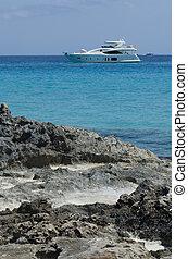 yacht moored near the rocks on the blue sea