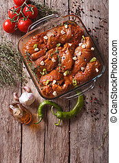 Meat in red marinade with spices in a bowl. vertical top...