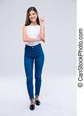 Smiling female teenager pointing finger up - Full length...