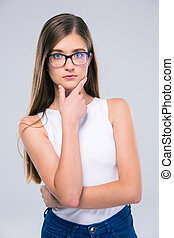 Portrait of a thoughtful girl in glasses standing isolated...