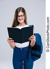 Portrait of a smiling female teenager reading book
