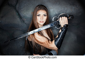 Beautiful girl holding a steel sword in his hand. Against...