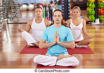 Yoga - Three persons sit in a lotus pose