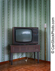 retro tv with wooden case in room with vintage wallpaper