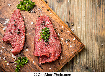Beef meat - Top view of raw beef meat slices on wooden board