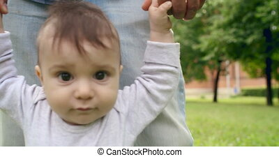 Cutie Trying to Walk - Cute baby boy looking at camera while...