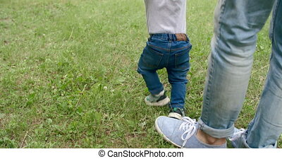 Walking with Daddy - Rear view of baby boy trying to walk...