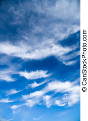 Cirrus and stratus clouds against bright blue sky, vertical...