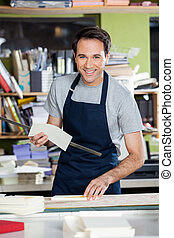 Smiling Worker Working At Table In Paper Industry - Portrait...