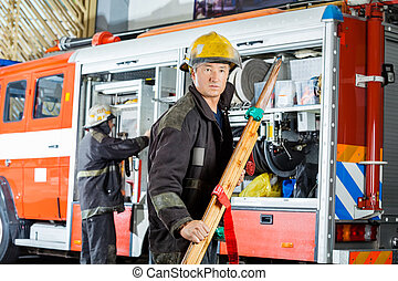 Confident Fireman Holding Wooden Stretcher - Confident...
