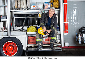 Confident Fireman Sitting In Truck At Fire Station - Full...