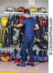 Firefighter Removing Uniform Hanging At Fire Station - Full...