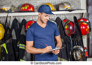 Firefighter Writing On Clipboard - Young male firefighter...