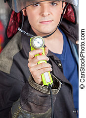 Confident Fireman Holding Torch At Fire Station - Portrait...