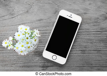 Smart phone with blank screen lying on wooden table, iphon...