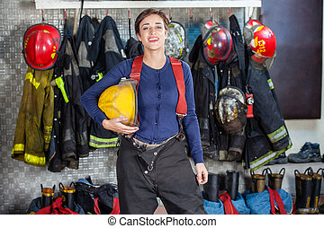 Confident Female Firefighter Standing At Fire Station -...