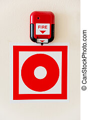 Fire alarm and a sign of alarm on the wall