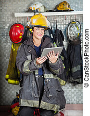 Smiling Firewoman Holding Digital Tablet At Fire Station -...
