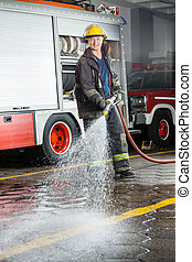 Smiling Fireman Spraying Water During Training - Portrait of...