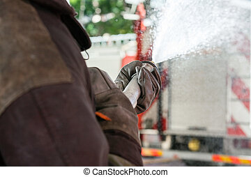 Fireman Spraying Water During Practice - Cropped image of...