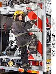Firewoman Climbing Truck At Fire Station - Rear view...