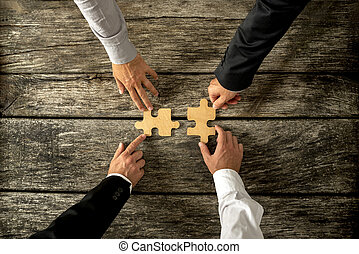 Four successful business men joining two puzzle pieces each...