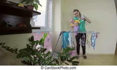 mom take baby clothes - young happy mother take clean baby...