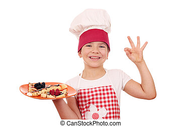happy little girl cook with crepes and ok hand sign