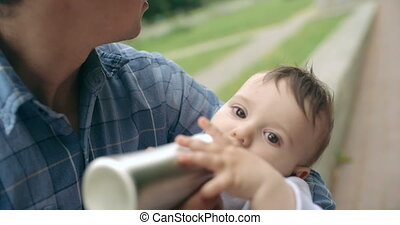 Time for some milk - Father feeding his baby son from bottle