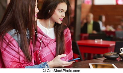 Two girl listening music with a smartphone