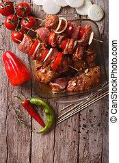 raw kebab in a spicy marinade on skewers. vertical top view...