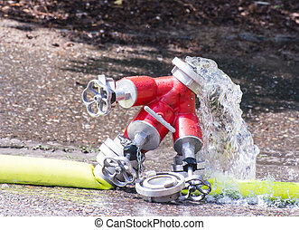 Valve and Firehose - Water splashing out of a valve for a...